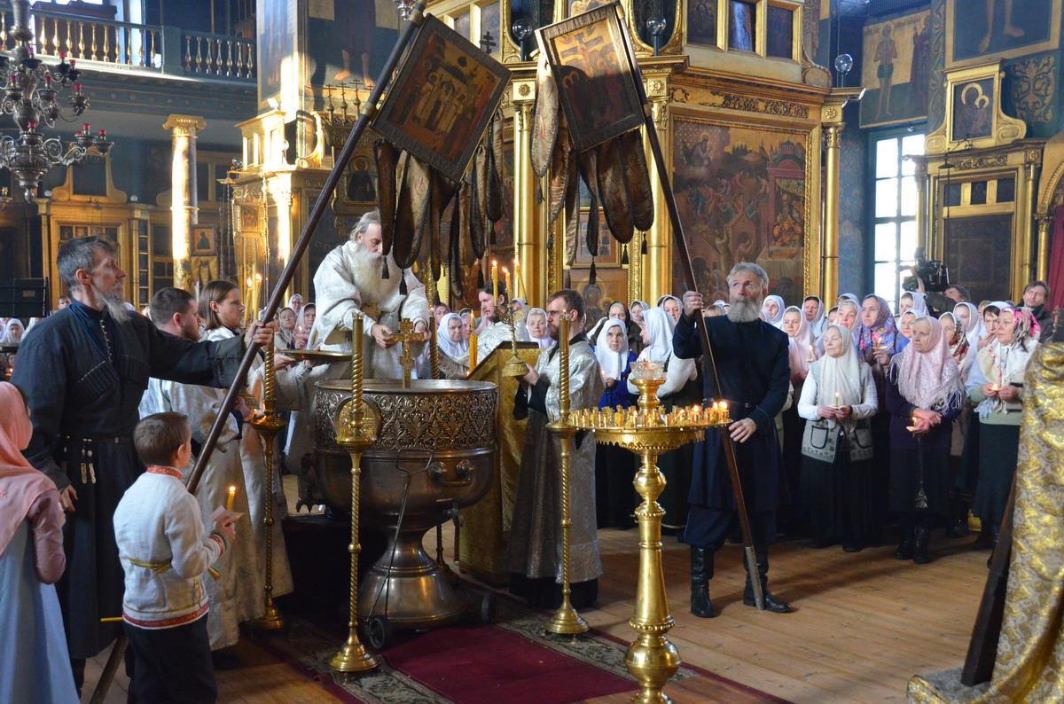При погружении Креста хоругви трижды наклоняются