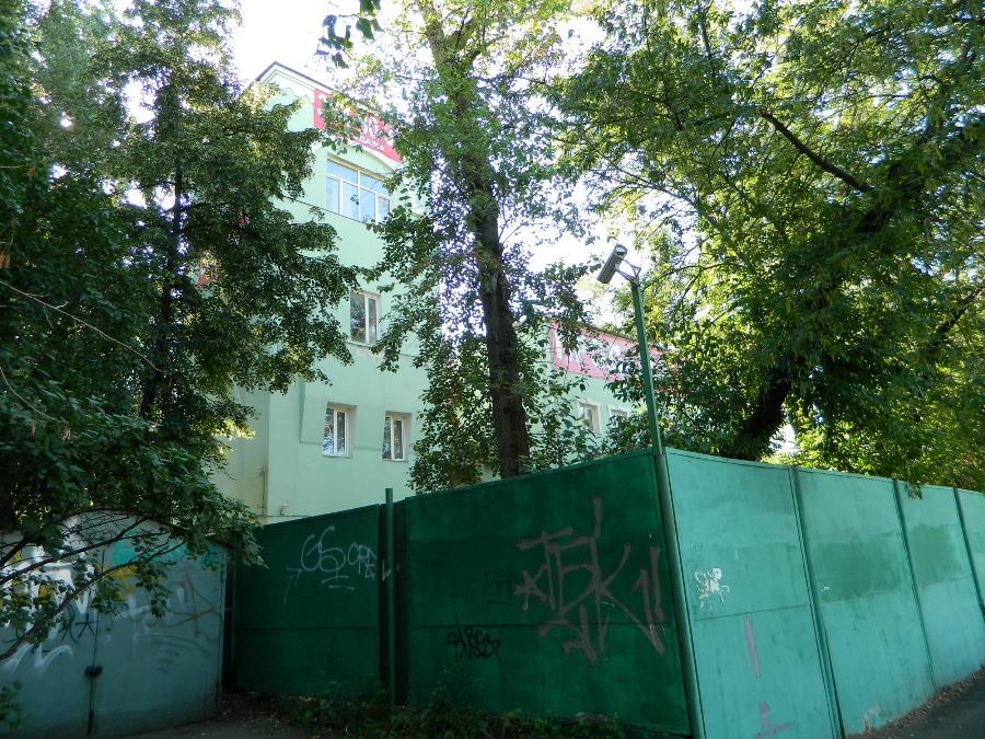 Строение №15 по Малой Андроньевской. Здание окружено высокими деревьями и обнесено глухим забором