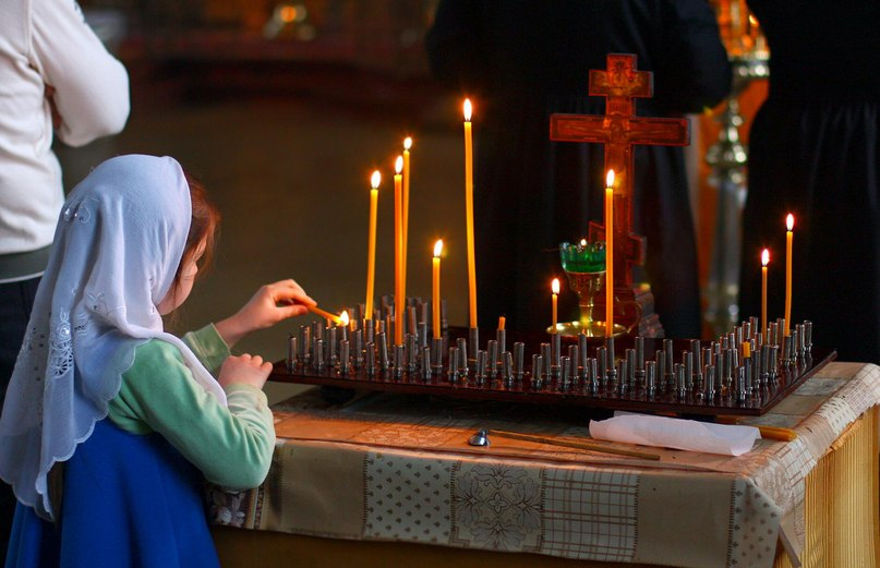 Девочка ставит свечу за упокой